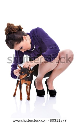 attractive young woman preparing  her dog for walking, isolated on white background - stock photo