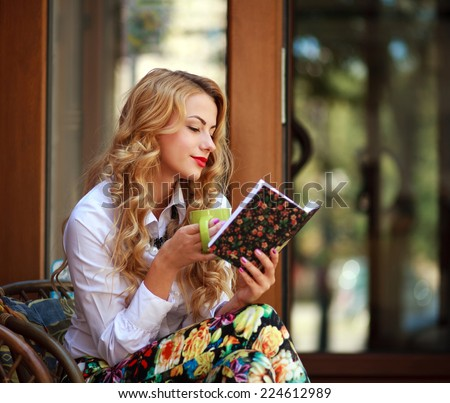 Attractive young woman reading book while drinking coffee at sunny day sitting in a chair outdoors - stock photo