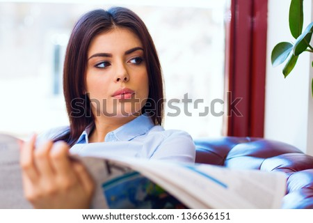 Attractive young woman reading the newspaper at office