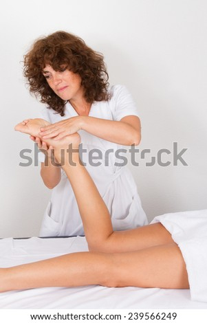 Attractive young woman receiving foot massage at spa center
