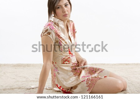 Attractive young woman relaxing and sitting on the carpet at home while listening to music with her earphones. - stock photo