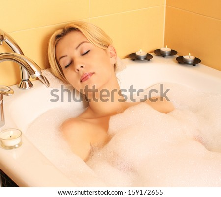 Attractive young woman relaxing in a bubble bath - stock photo