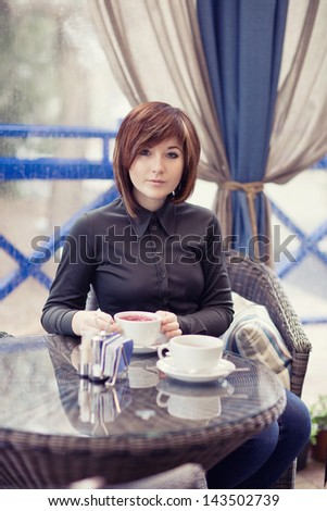 attractive young woman relaxing in cafe - stock photo