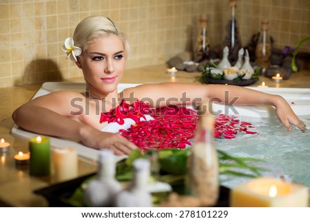 Attractive young woman relaxing in jacuzzi with flower petals - stock photo