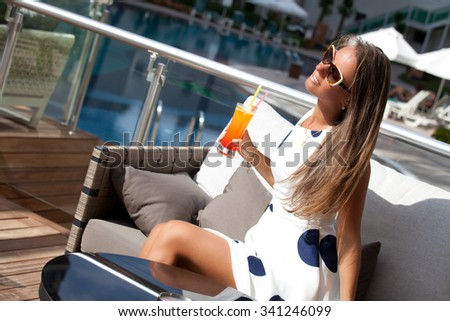 Attractive young woman relaxing on a deck chair by the poolside with cocktail, sunny day, outdoor. Girl at travel spa resort pool. Summer luxury vacation.  - stock photo