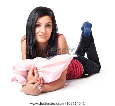 Attractive young woman relaxing with pillow in her hands