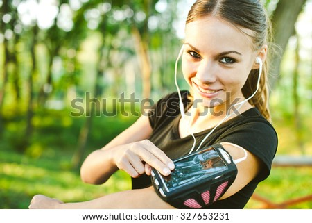 Attractive young woman runner showing her phone wearing in armband during training with earphones and music. Pointing at gadget display