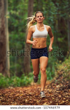 Attractive Young Woman Running in the Forest - stock photo