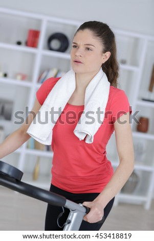 attractive young woman runs on a treadmill - stock photo