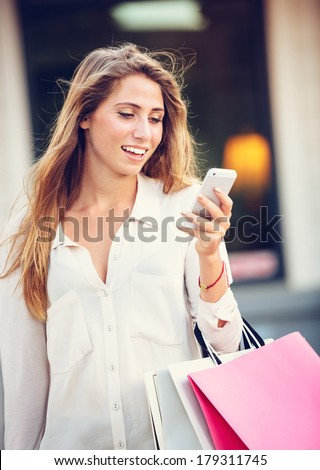 Attractive young woman shopping at the mall using cell phone - stock photo