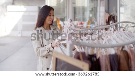 Attractive young woman shopping for clothing - stock photo