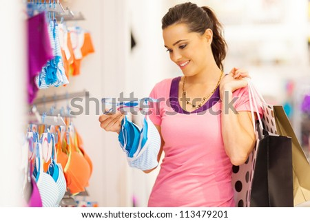 attractive young woman shopping for underwear in clothing store - stock photo