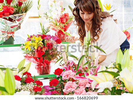 Attractive young woman shopping in an outdoors fresh flowers market stall, buying and picking from a large variety of colorful floral bouquets during a sunny day in the city. - stock photo
