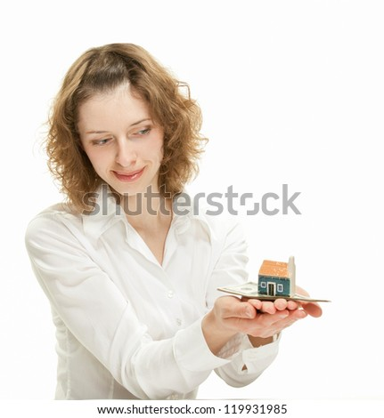 Attractive young woman showing dollar banknotes and small house; concept of investment in real estate - stock photo