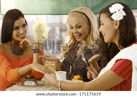 Attractive young woman showing engagement ring to friends at outdoor cafe. All smiling. - stock photo