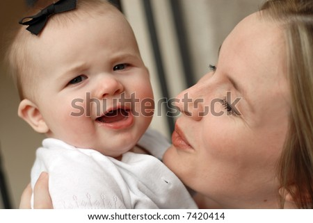 Attractive young woman showing off her pretty little baby girl