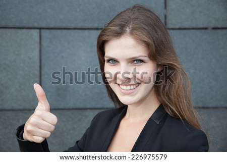 Attractive young woman showing thumbs up - stock photo