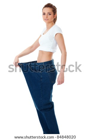 Attractive young woman shows her old huge jeans, shoot over white background - stock photo