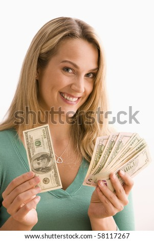 Attractive young woman shows off a selection of money she is holding.  Vertical shot. - stock photo