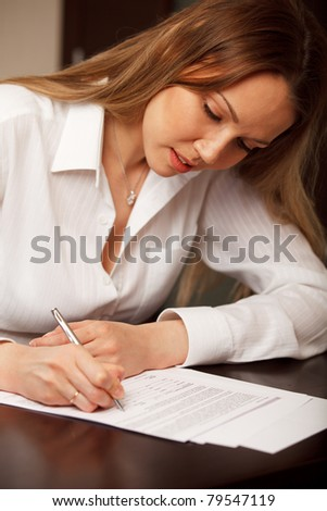 Attractive young woman signing contract - stock photo