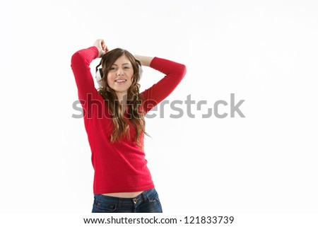 Attractive young woman singing and dancing while listening to music on her headphones, wearing a red top, isolated against a white background. - stock photo