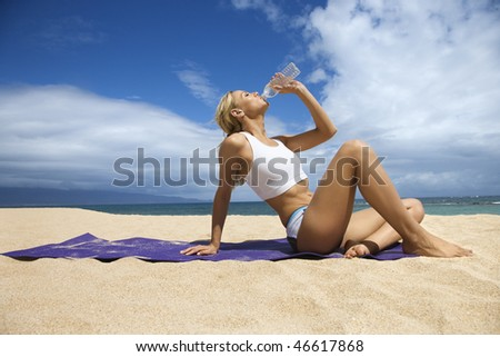 Attractive young woman sits back and drinks water after exercising on the beach. She is sitting on a blue towel and the ocean is in the distance. Horizontal shot. - stock photo