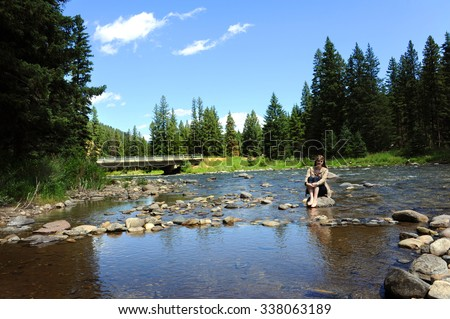 Attractive young woman sits barefoot with jeans rolled up, in the middle of the Gallatin River in Montana.  She is thoughtful and pensive as she sits and enjoys time alone. - stock photo