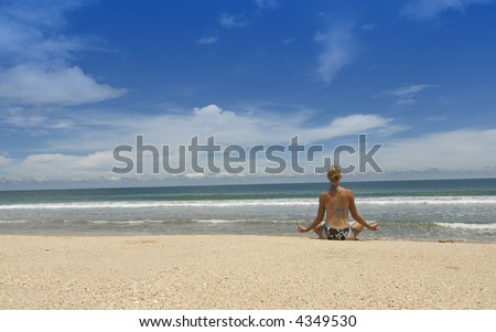 attractive young woman sits on the beach doing Yoga - stock photo