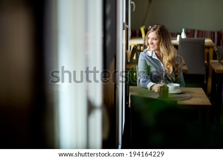 Attractive young woman sitting alone in cafe looking out window - stock photo