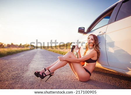 Attractive young woman sitting at a car and drinking water - stock photo