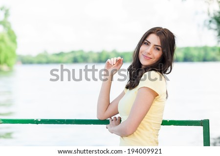 Attractive young woman sitting beside a scenic lake surrounded by water and trees as she enjoys a sunny spring day out in nature - stock photo