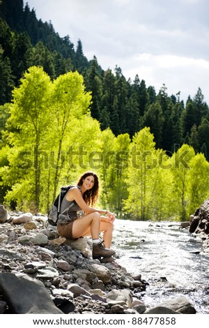 attractive young woman sitting by a mountain stream - stock photo