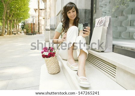 Attractive young woman sitting down a the steps of a shopping street store in a city, holding and using a smart phone while having a break, smiling outdoors.