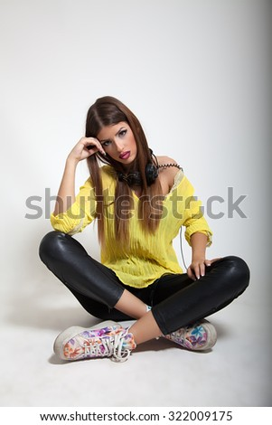Attractive young woman sitting down on gray background. - stock photo