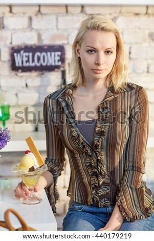 Attractive young woman sitting in cafeteria having sundae, looking at camera. - stock photo