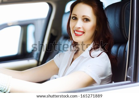 Attractive young woman sitting in car in car center - stock photo