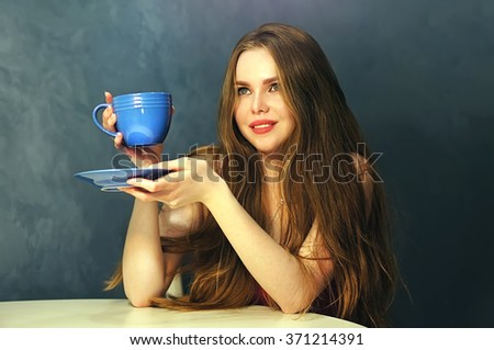 Attractive young woman sitting in restaurant. Beautiful blonde posing with a cup of coffee in her hand.  - stock photo