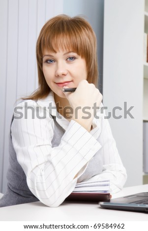 attractive young woman sitting on a background of office interior - stock photo