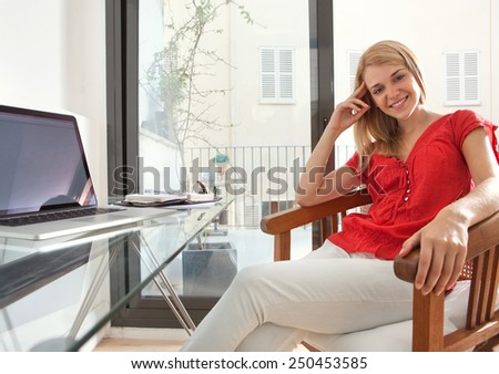 Attractive young woman sitting on a chair in her home office desk using a laptop computer to work on, home interior. Student girl smiling using technology at home. Lifestyle and technology indoors. - stock photo