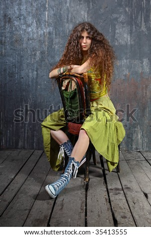 Attractive young woman sitting on a chair on wooden floor in a studio - stock photo