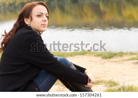 Attractive young woman sitting on a river bank watching something intently looking towards the right of the frame across copyspace - stock photo