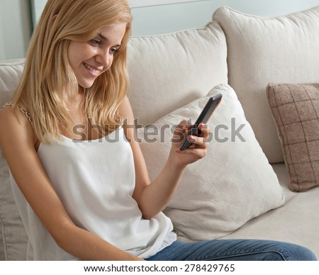 Attractive young woman sitting on a sofa at home, using a smartphone, networking on her cell phone, smiling. Student girl using mobile phone internet at home, interior. Home technology lifestyle. - stock photo