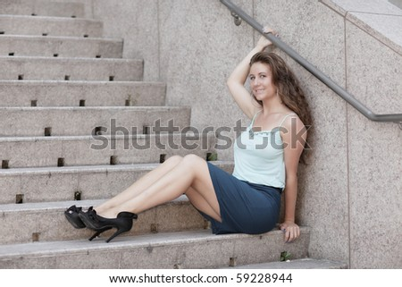 Attractive young woman sitting on a staircase of an office building