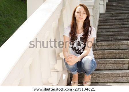 Attractive young woman sitting on a steep flight of steps with a painted white balustrade clasping her knee with her hand looking at the camera with a serious expression - stock photo
