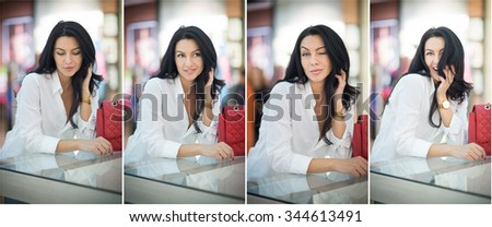 Attractive young woman sitting on a table in shopping center. Beautiful fashionable young lady in white shirt in mall. Casual long hair brunette posing smiling and teasing, indoors shot - stock photo
