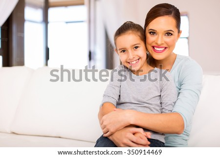 attractive young woman sitting on couch with her daughter - stock photo