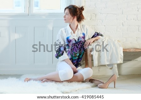 Attractive young woman sitting on floor at home, turning head away, daydreaming. - stock photo