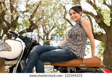Attractive young woman sitting on her new motorbike feeling proud in a street with trees behind her, smiling at the camera. - stock photo
