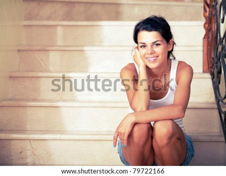 Attractive young woman sitting on stairs and smiling