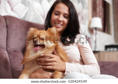 Attractive young woman sitting on the couch and keeps the dog. She smiles and looks at her pet.
